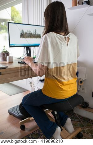 Young Woman Working At Home Using An Ergonomic Kneeling Chair Seen From Her Back.