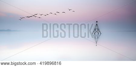 Birds Flying Over A Cardinal Sailing Marker At Sunset On The Loughor Estuary, Llanelli, South Wales,