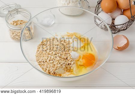 Cooking Oatmeal Pancakes With Bananas. Eggs, Buttermilk, Sugar, Vanilla, Oatmeal In A Bowl On A Whit