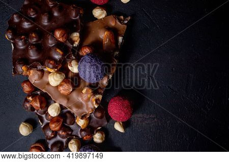 Chocolate Bar, Crushed Pieces Of Dark Chocolate And Nuts. Praline Chocolate Sweets. Copy Space