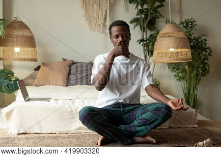 Young African Man Practicing Yoga Lesson, Doing Alternate Nostril Breathing Exercise