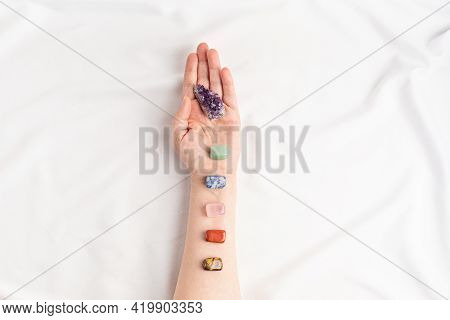 Healing Reiki Chakra Crystals On Womans Hands. Gemstones For Wellbeing, Meditation, Relaxation