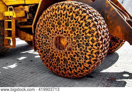 Yellow Metal Chains With Sandy Dirt On Huge Tire Of Construction Machine. Chains With Ring Chain Lin