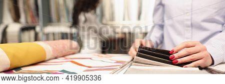 Woman Shopper Choosing Curtain Fabric Sample In Store Closeup