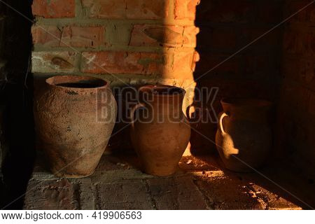 Old Barbecue Oven, With Ancient Clay Pots And Stone Millstones. A Jug Of Clay The Stove
