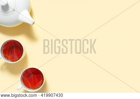 Teapot And Two Cups Of Hot Aromatic Tea On Yellow Background. View From Above.  Flat Lay, Top View,