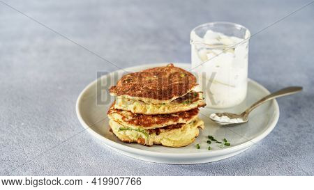 Vegetable Zucchini Fritters In Stack With Sour Cream And Chive, Light Background, Copy Space. Clean