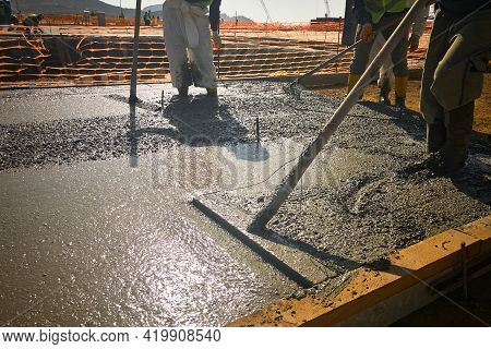 Construction Workers Use Bull Float To Level, Flatten And Smooth Concrete Of Cast In Place Foundatio