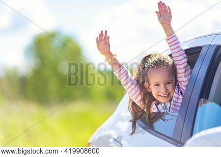 Family Travel Concept By Car. Happy Smiling Child Girl Looking From The Car Window. Summer Backgroun