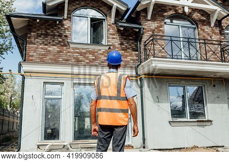 Rear View Of The Builder Of The Middle-aged Inspector Looking Towards The Unfinished House. Construc