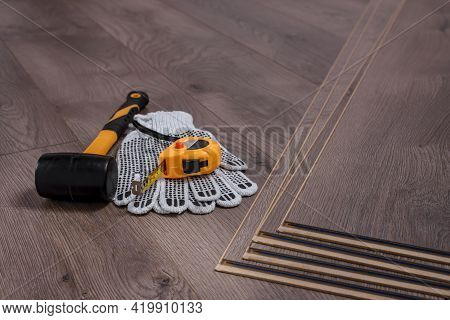Rubber Hammer, Protective Gloves And Tape Measure On Laminate Floor, Carpenter Tools For Laying Lami