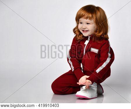 Cute Smiling Red-haierd Little Preschooler Girl Wearing White Sneakers, Warm Tracksuit Sportswear An