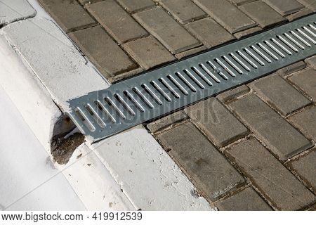 Iron Grate Of A Drainage System For Storm Water Drainage From A Pedestrian Sidewalk