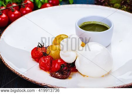 Burrata Cheese With Baked Cherry Tomatoes And Pesto Sauce On White Plate.