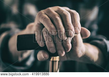 Old Man's Wrinkled Hand With A Walking Cane. Toned.
