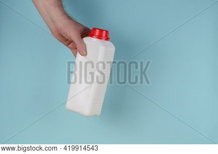 Hand Holds White Container With Lid For Liquids On Blue Background. Rectangular Plastic Generic Bott