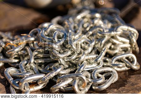 A Bunch Of Chrome Chain. A Thick Metal Chain Lies In A Large Pile On The Stone. Very Close-up Of The