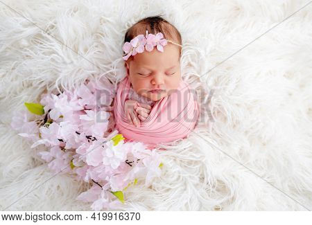 Swaddled beautiful newborn baby girl with flower wreath on her head sleeping in white fur. Cute female infant child photoshoot in studio. Adorable kid napping