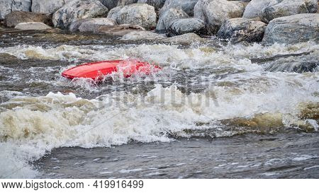 kayaker rolling and floating upside down after surfing a wave in the Poudre River Whitewater Park.