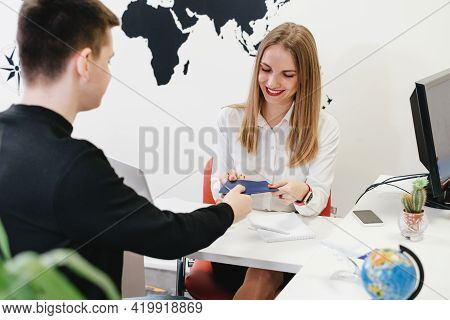 Travel Agent Having A Client In Light Modern Office Of Tour Agency, Giving Passport After Check-in O