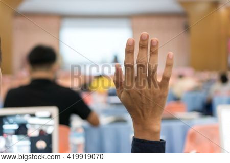 Audience Raising Hand While Speaker On Stage At Conference To Answer Question While Speaker Speech A