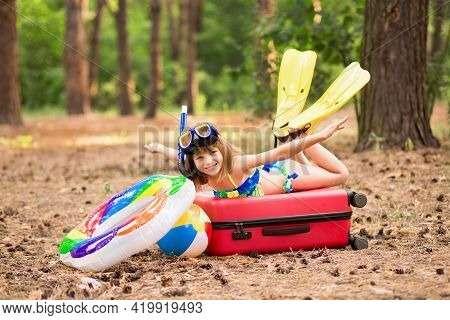 Enthusiastic Little Girl In Swimsuit, Fins And Swimming Mask With Circle And Swimming Ball Packed Su