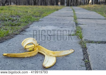 A Carelessly Discarded Banana Peel In The Form Of Garbage Lies On A Concrete Footpath On The Way To