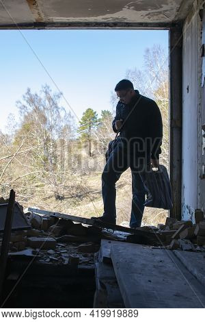 A Man With Things Came To The Destroyed House And Sadly Examines The Wreckage Of The Broken Structur