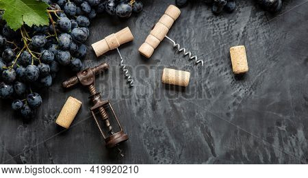 Many Different Corkscrews Varieties With Open Wine Corks On Dark Concrete Background, Black Grapes.