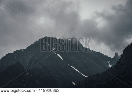 Dark Atmospheric Mountain Landscape With Black Pointy Rocky Peak In Gray Cloudy Sky. Lead Gray Low C