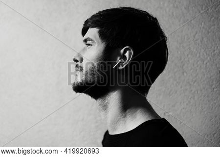 Black And White Photo; Side Portrait Of Young Man With Wireless Earphone In Ears On Textured Backgro