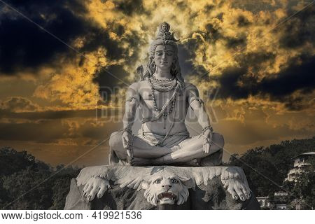 Statue Of Meditating Hindu God Shiva Against The Sky And Clouds On The Ganges River At Rishikesh Vil