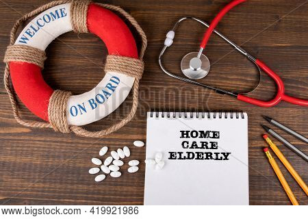 Home Care Elderly. Note Paper, Stethoscope And Office Supplies On A Wooden Table