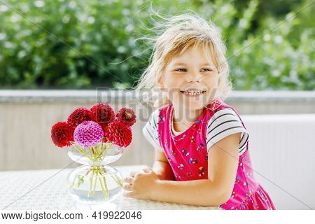 Portrait Of Little Toddler Girl Admiring Bouquet Of Blooming Red And Pink Dahlia Flowers. Cute Happy