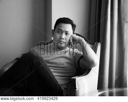 Sad Man Sitting Next To Window In Dark, Looking With Empty Look, Thinking Contemplating Depression C