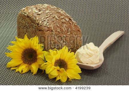 Multi-grain-bread and oleo on a cooking spoon with sunflower blossoms poster