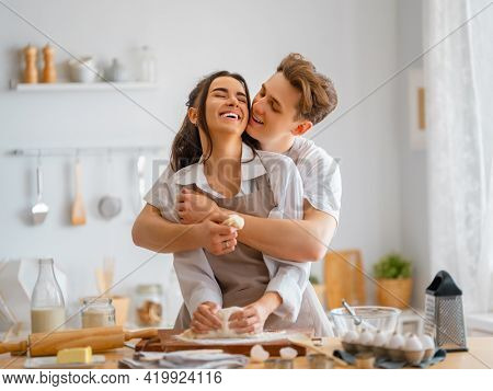 Happy loving couple is preparing the pastry in the kitchen.