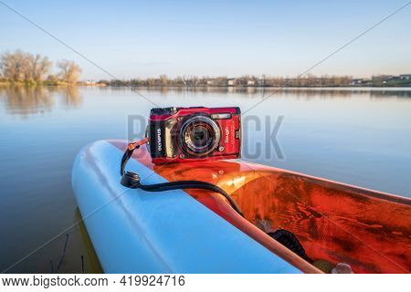 Fort Collins, CO, USA - May 6, 2021: Compact, waterproof Olympus Stylus Tough TG-5 camera on a rear deck of a stand up paddleboard by Mistral, early spring lake scenery in Colorado.