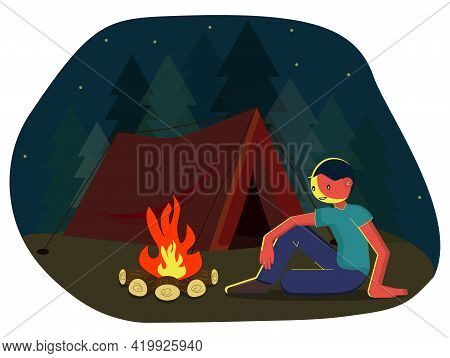 A Traveling Man Sits On The Grass By The Fire. A Young Man Is Sitting By The Fire. Smiling Tourist R