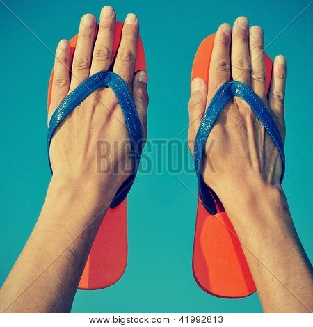 someone wearing flip-flops on his hands over the blue sky poster