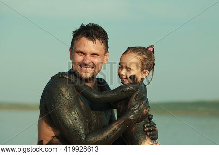 Therapeutic Mud For The Body. Mud Baths On The Lake. A Man And A Child Are Smeared With Clay. Family