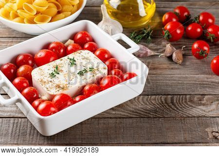 Baked Feta Pasta. Tomatoes Drizzled With Olive Oil In A Baking Dish With A Feta Cheese Block In The