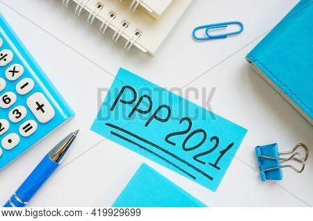 Ppp Loan 2021 Handwritten Words On A Blue Piece Of Paper.