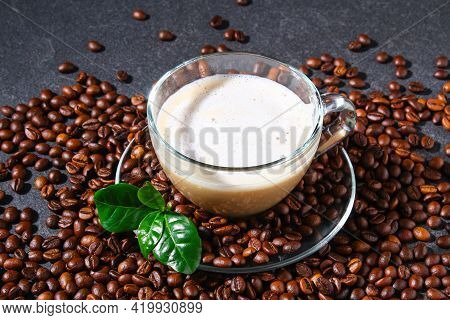 Cup Of Coffee On A Gray Table With Coffee Beans And Coffee Leaves. Closeup.