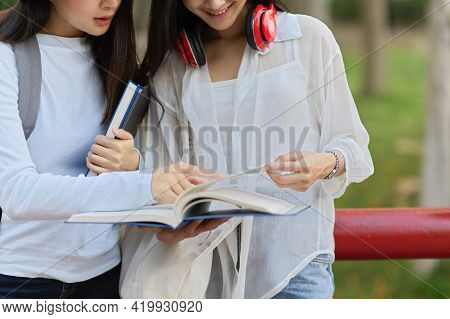 Two Female University Students Outdoor Study, Tutoring To Prepare Their Up Coming Exam At The Park