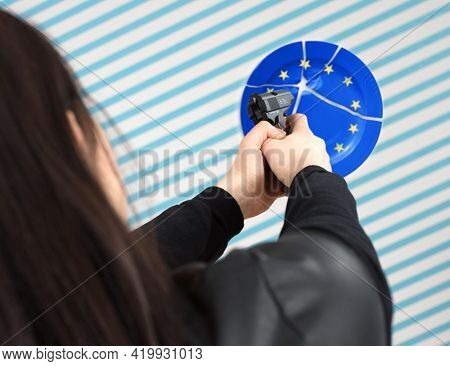 Young woman shoots a pistol gun at the EU symbol blue circle with stars. The concept of Brexit and EU collapse