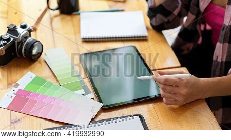Side View Of Female Designer Student Doing Assignment With Digital Tablet And Designer Supplies And