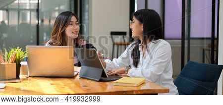 Two Female Students Having Conversation While Doing Group Assignment With Laptops