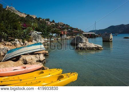 Kalekoy, Turkey - 20 October, 2019: Kayaks and old boat leaved unused on shore of Mediterranean sea at Kalekoy Castle's village, Popular tourist destination