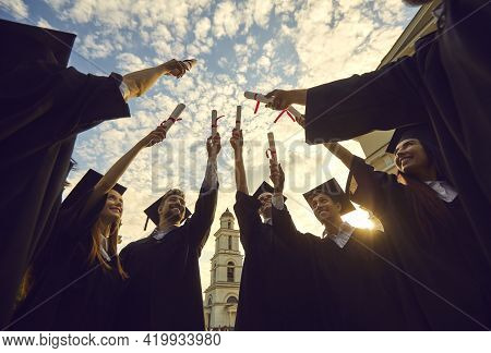Happy Young Graduates In Black Mantle Proudly Raising Their Scrolls Of Diplomas Up Against The Sky.